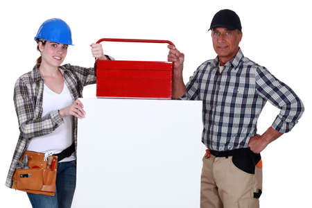 Tradespeople posing with their toolbox and a blank sign photo