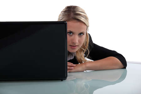 Blond woman peering from behind laptop photo