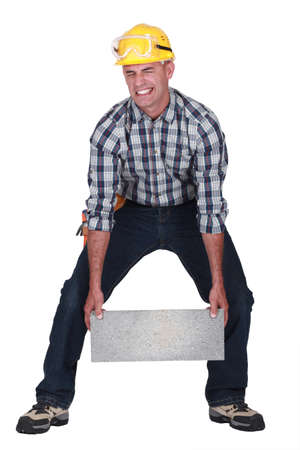 Man struggling to carry building block