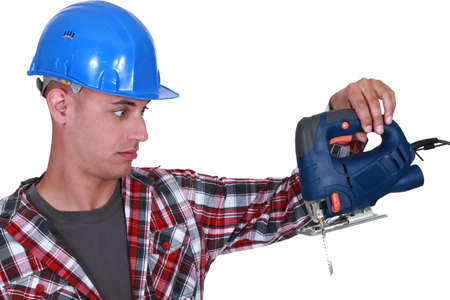 consternation: craftsman looking at his drill very surprised