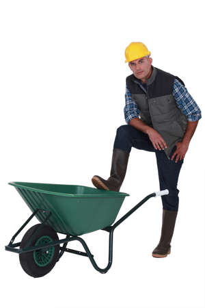 barrow: Man resting foot on wheelbarrow