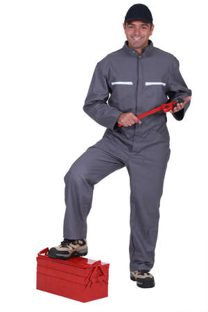 jumpsuit: Tradesman with his foot propped on a toolbox Stock Photo