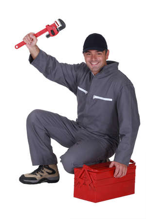 coverall: Tradesman posing with his toolbox and a pipe wrench Stock Photo