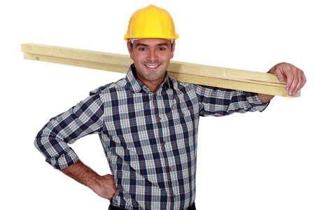 mirthful: Cheerful carpenter carrying timber Stock Photo