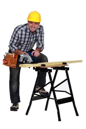 carpenter's sawdust: A mature carpenter with a circular saw  Stock Photo