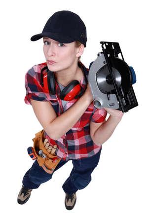 mitre: Female carpenter wielding circular-saw Stock Photo