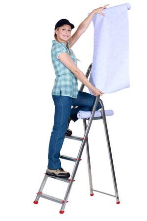 refurbishing: Woman putting up wallpaper Stock Photo