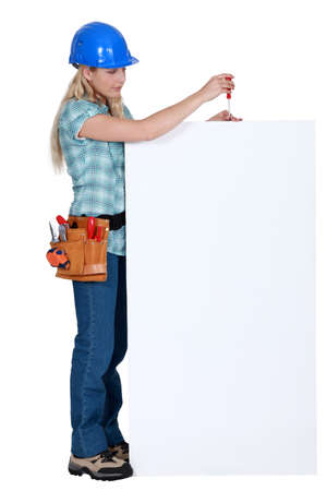 craftswoman: craftswoman fixing an ad board Stock Photo