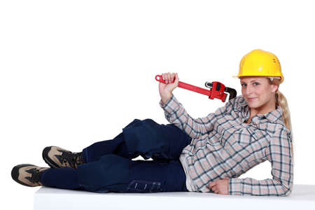 Attractive blond plumber laying with wrench photo