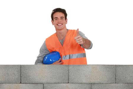 Positive mason stood by wall photo