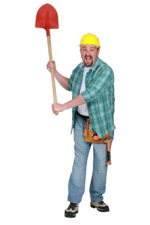 A delirious tradesman holding up a spade photo