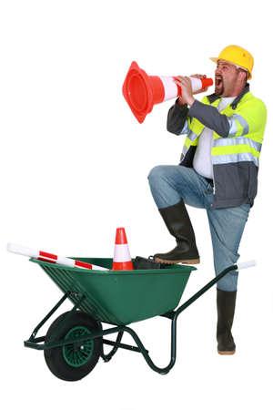Laborer shouting into traffic cone Stock Photo - 15289588