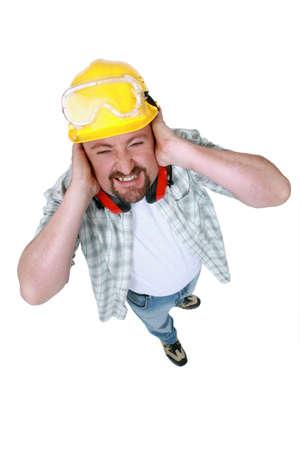 injurious: Paisaje imagen de trabajador que cubre sus o�dos