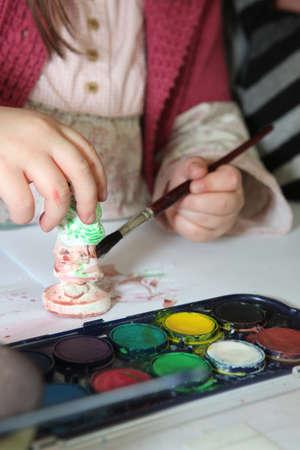 plaster of paris: Child painting a plaster figurine