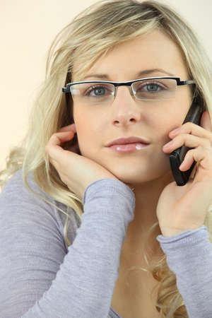 Young blond woman with telephone photo