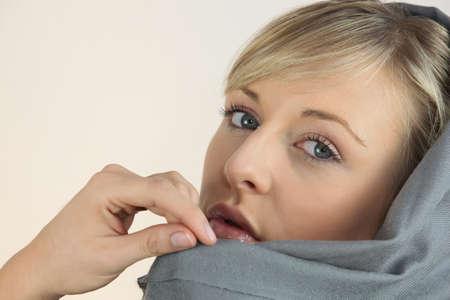 rubia ojos azules: Mujer rubia envuelta en una bufanda gris