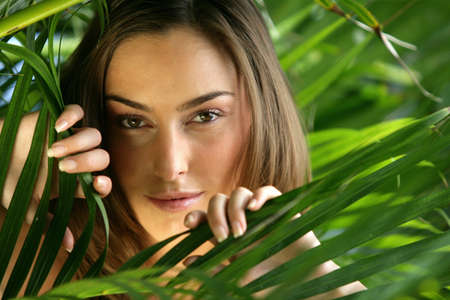 face in tree bark: woman hiding behind a plant Stock Photo