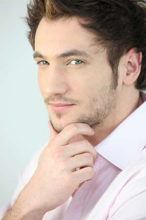 speculating: Handsome young man with his hand on his chin Stock Photo