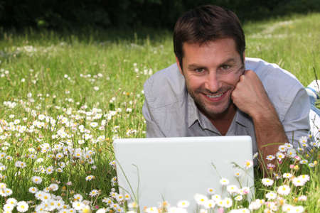 man on the grass with laptop photo
