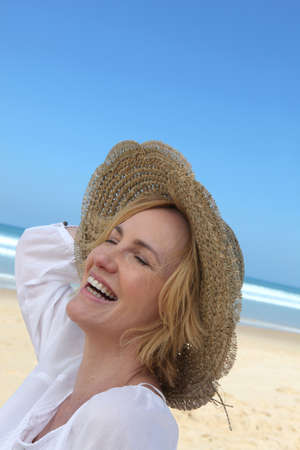 Woman laughing on the beach photo