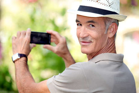 hobbyist: Middle -aged man taking photo whilst wearing straw hat