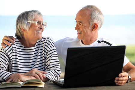 Senior couple in the garden with laptop and book photo