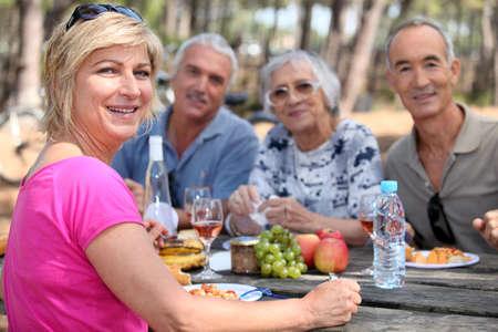 ancianos caminando: Amigos maduros que comen al aire libre Foto de archivo