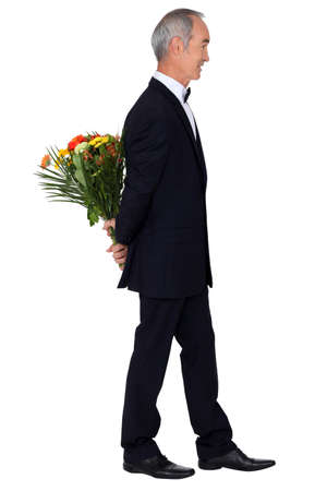 anniversary sexy: Man in an evening suit with a bouquet of flowers Stock Photo