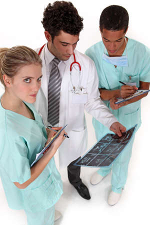 A team of medical professionals discussing the results of a patients x-ray photo
