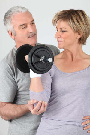 Man helping a woman lift a dumbbell photo