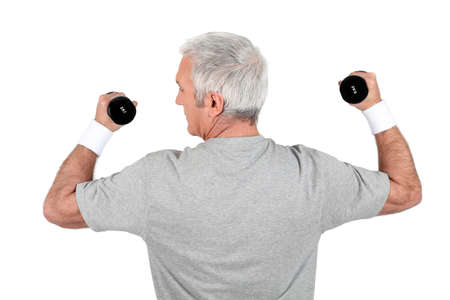 Grey-haired man doing weights photo