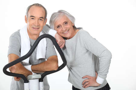 Senior couple using gym equipment photo