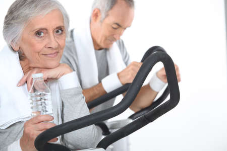 65 years old: Couple exercising together at the gym