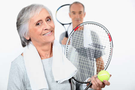 jugando tenis: Pareja de ancianos jugando al tenis