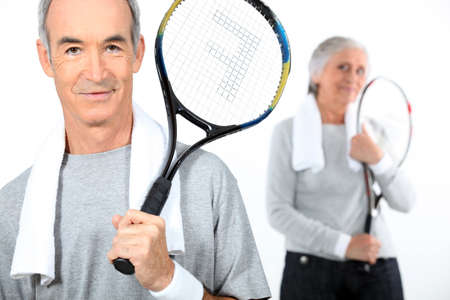 Senior couple with tennis rackets photo