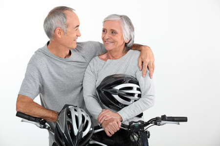 looking around: Elderly couple riding their bikes together