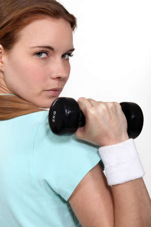 determined: A determined woman lifting a dumbbell