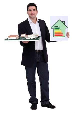 energy efficient: man holding an architectural model and an energy consumption label