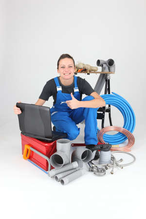 Female plumber with tools of the trade and a laptop computer photo