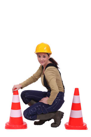 road worker: Female road worker kneeling by cones Stock Photo