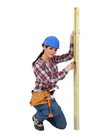 Woman measuring a piece of wood Stock Photo - 15391520