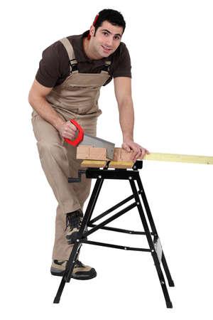 miter: Man using miter to saw wood