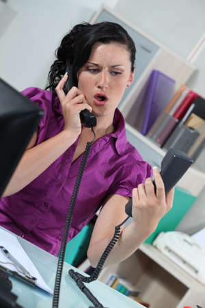Stressed secretary answering two telephones photo