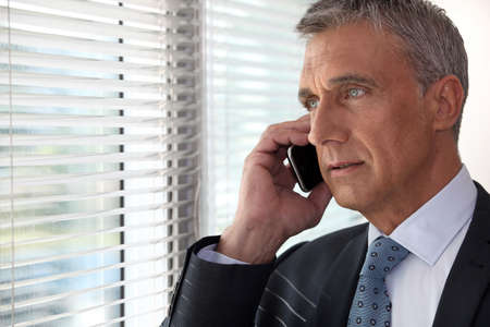 executive affable: Executive phone in front of window Stock Photo