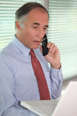 50 years old man: mature businessman on the phone looks stunned Stock Photo