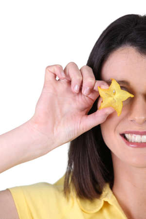 Woman covering her eye with a slice of star fruit photo