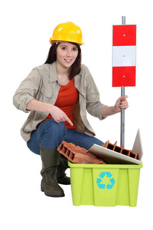 Female construction worker warning you to recycle old material photo