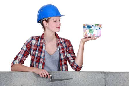 stonemasonry: Woman holding a house made of money