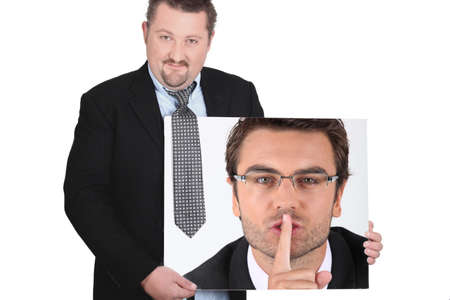 confidentiality: moon-faced man wearing coat and tie showing picture of young man with finger in mouth Stock Photo
