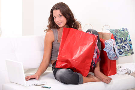 later: Woman surrounded by bags shopping on-line